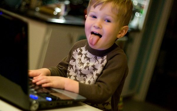 Little kid sticking out his tongue while using laptop