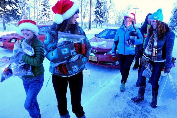 Students giving out presents with Santa hats