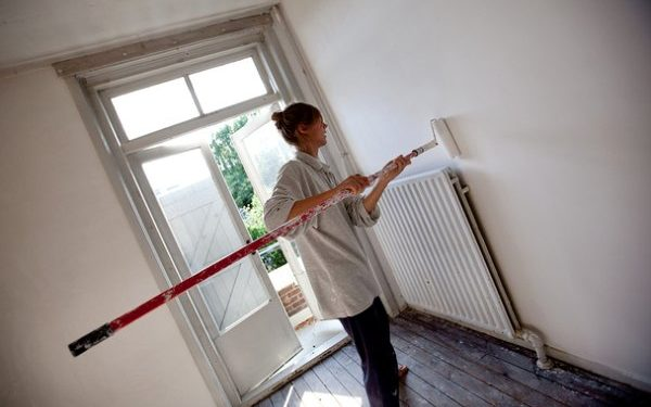 Woman painting a hallway wall