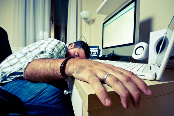 Man slumped over in front of computer