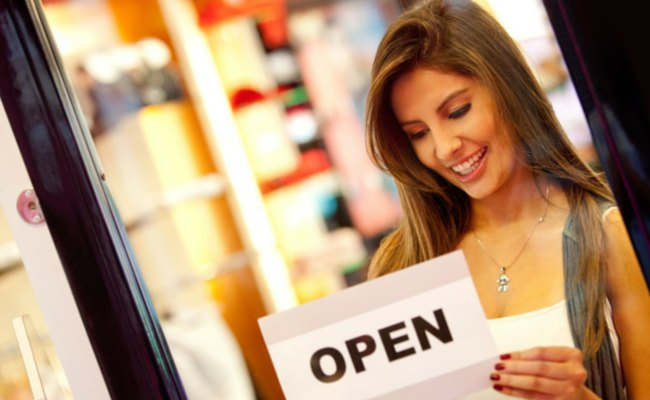 woman placing open sign on door of store