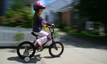 Girl riding bike with training wheels