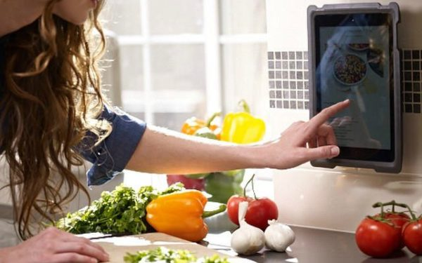 Woman using iPad while cooking