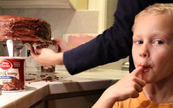 kid licking fingers next to birthday cake