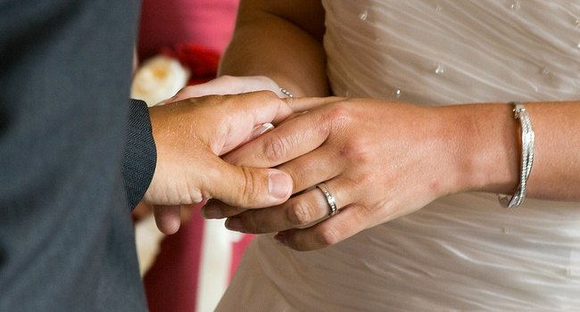 close up of couple holding hands during wedding ceremony