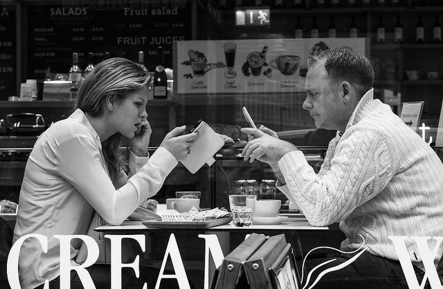 Man and woman using smartphones at restaurant