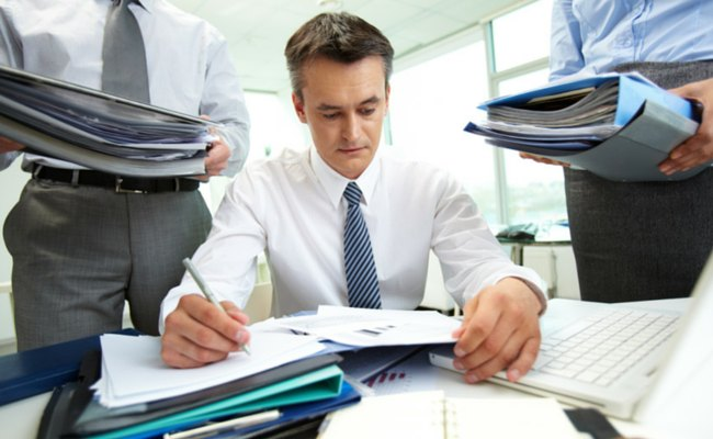 Man working at desk, coworkers with binders