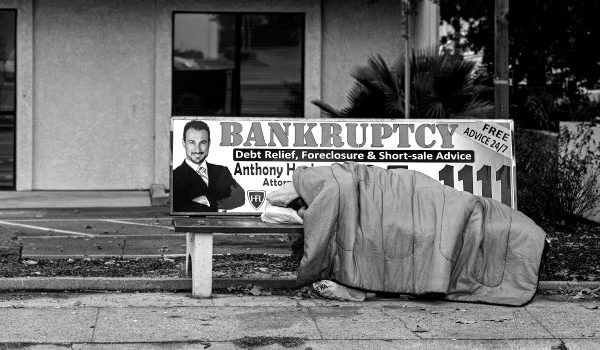 homeless person sleeping on bench with 'bankruptcy' ad - chapter 7 bankruptcy vs chapter 13