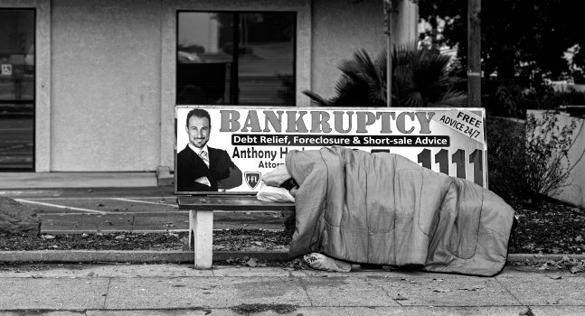homeless person sleeping on bench with 'bankruptcy' ad
