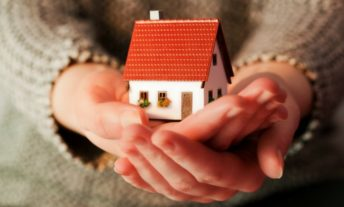 Woman holding miniature house how to save for a house down payment on a house