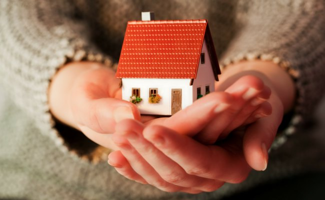 Woman holding miniature house how to save for a house down payment