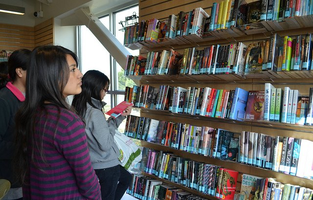 Teens browsing book collection at library