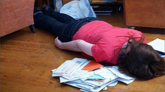 woman face-down in pile of mail and bills