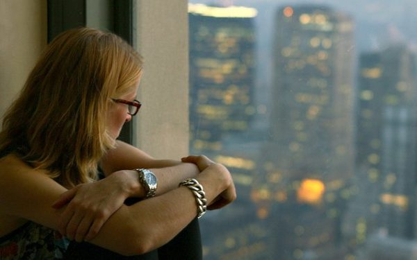 woman looking at city out the window