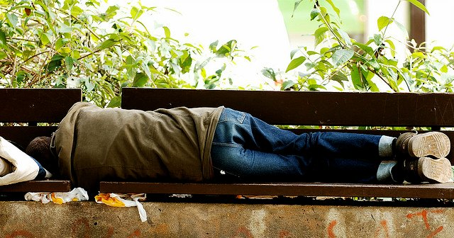 young homeless man sleeping on a park bench