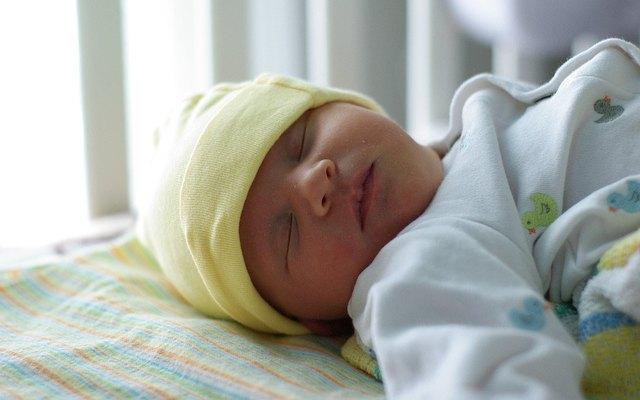 newborn baby sleeping in crib