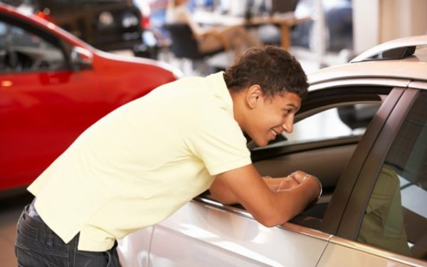 young man looking at new car