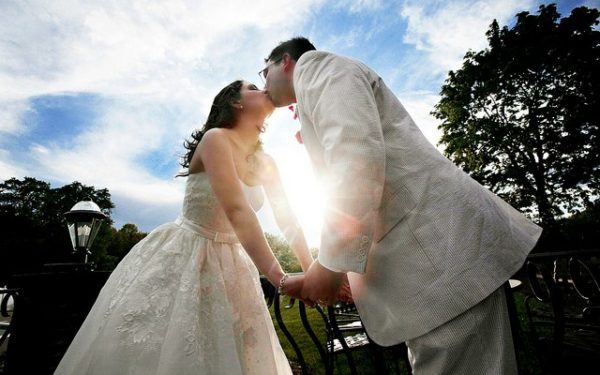 bride and groom kissing outdoors frugal ideas for a cheap wedding on a budget