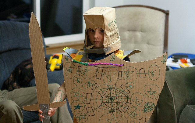 child in cardboard suit of armor and cardboard sword and shield