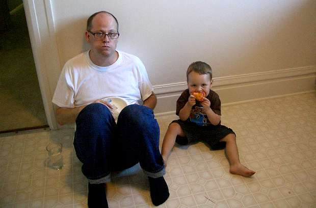 dad and son eating on kitchen floor