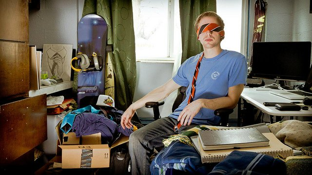 man in cluttered room wearing tie as blindfold