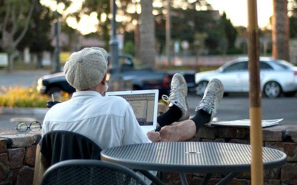 older man on laptop at coffeeshop