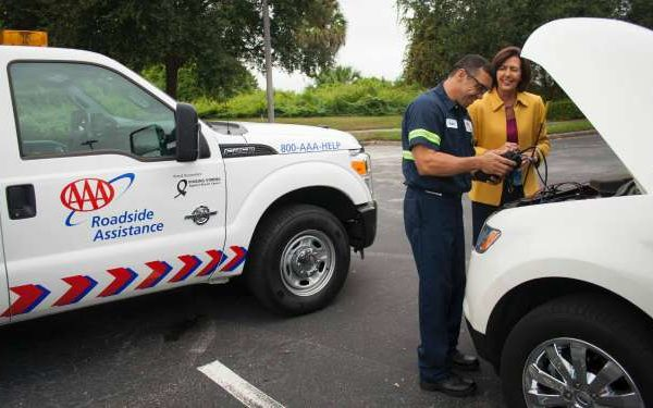 AAA driver helping woman with broken-down car