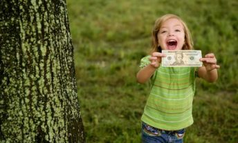 child holding $10 bill - bank account for kids