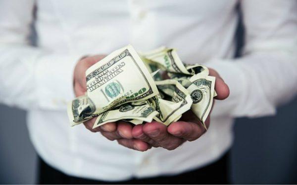 man holding crumbled hundred dollar bills