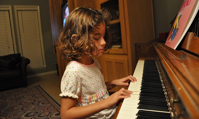 young girl practicing piano