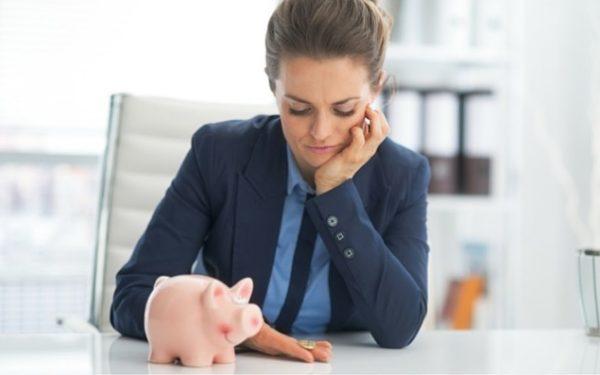 woman looking at piggy bank