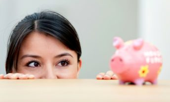 woman looking at piggy bank - basics of an IRA for retirement investing