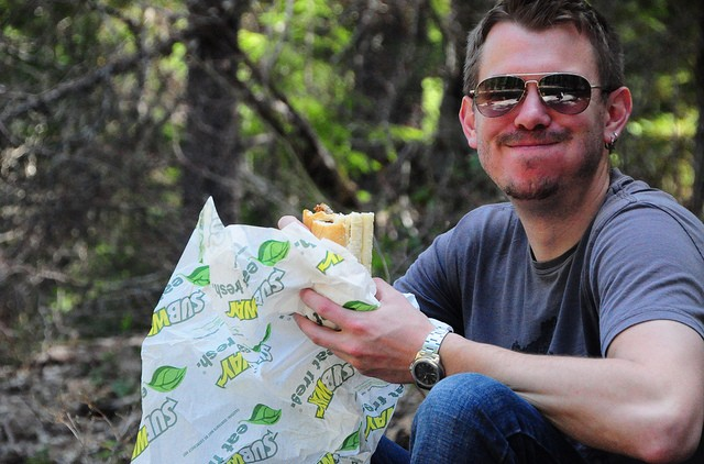 man eating subway sandwich