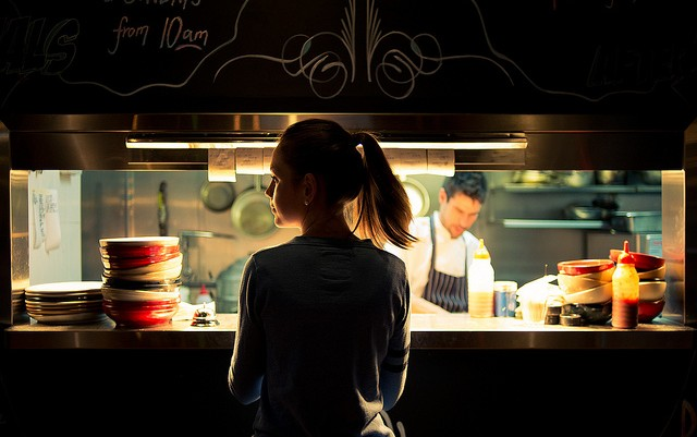 waitress and cook at restaurant kitchen window