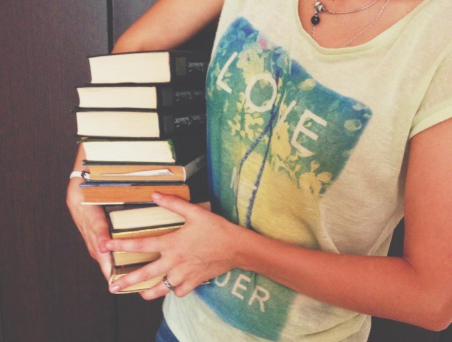 young woman holding armful of books