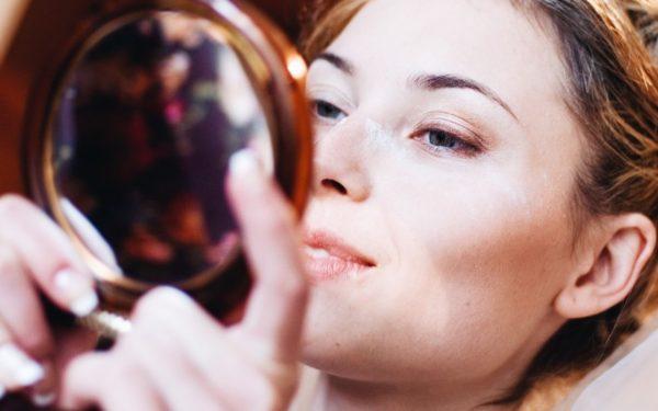 wealthy woman looking into makeup mirror