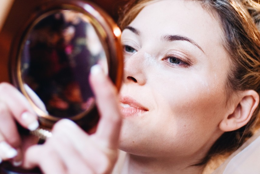wealthy woman looking into makeup mirror
