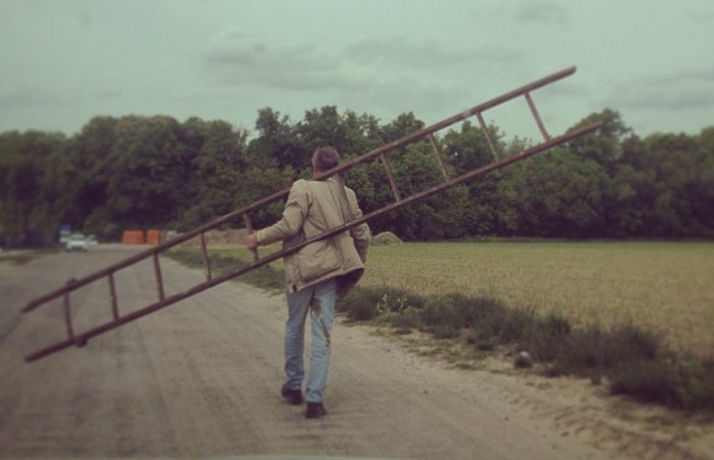 man carrying a ladder down the road