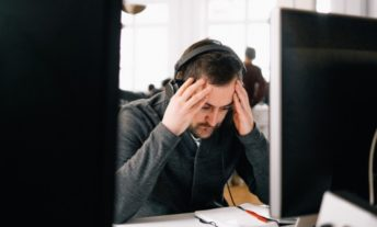 stressed man at a desk on phone