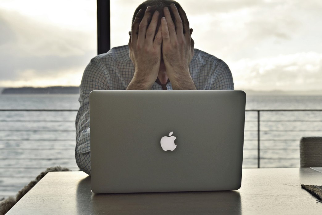 man stressed at computer - common investing mistakes