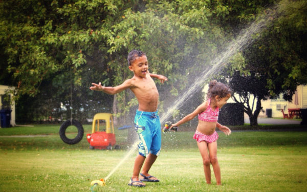 kids splashing in sprinkler on a hot summer day