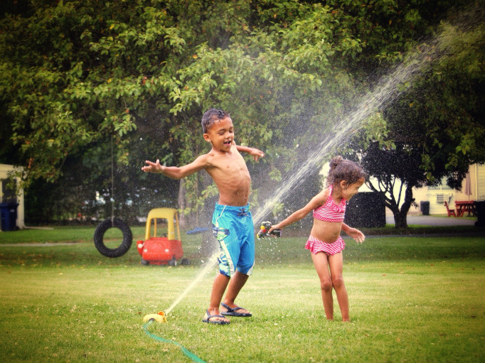 kids splashing in sprinkler on a hot summer day