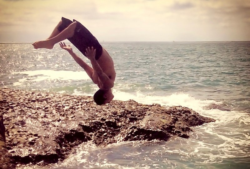 man flipping upside down off rocks
