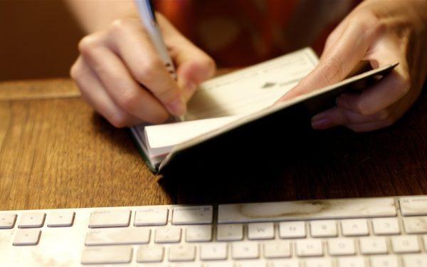 writing a check at the computer