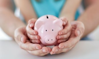 parent and child with piggy bank - how to open a roth ira for your child