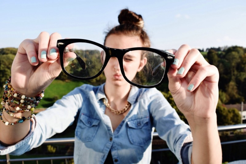 woman looking at glasses - how much does lasik cost?