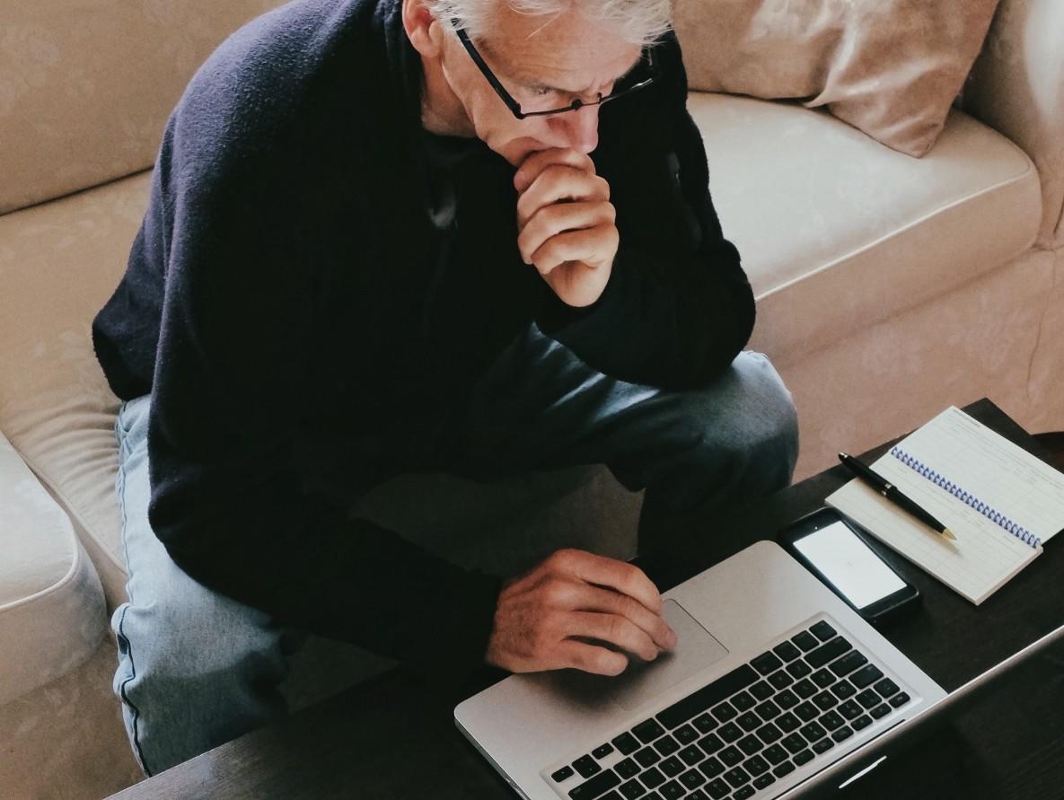 man using laptop - etrade vs td ameritrade