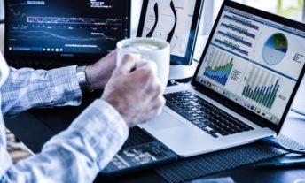 man looking at stock charts and financial information
