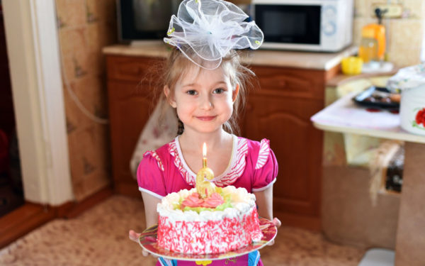 child holding homemade birthday cake
