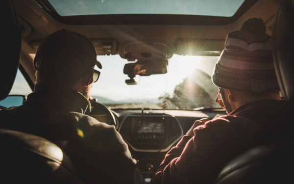 two men driving a car - low income car insurance